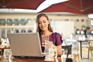Kvinde laver blog på sin computer i offentligheden