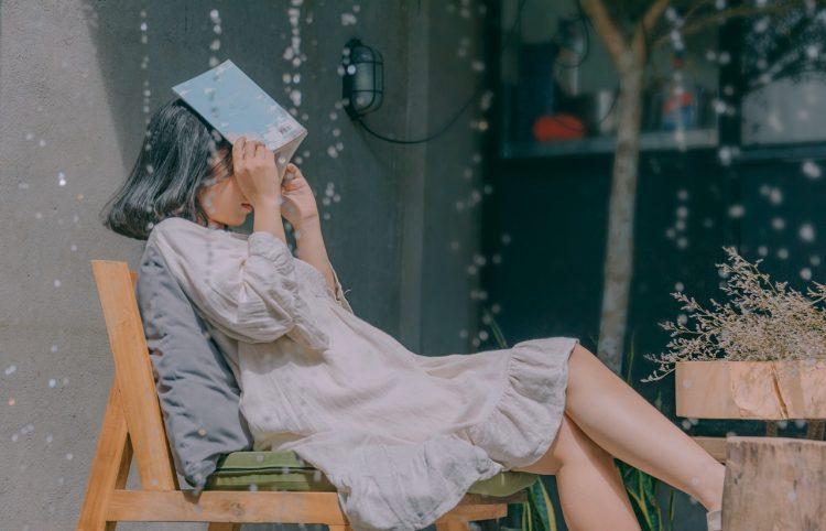 Kvinde sidder med bog over hovedet pga regn